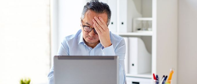 Man at desk in front of computer frustrated