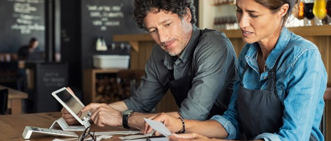 Business partners go through tax documents to determinate whether they need to apply for a filing extension.